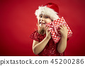adorable little girl in a Christmas dress in a Santa's hat with a christmas gift 45200286