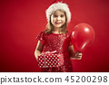 adorable little girl in a Christmas dress in a Santa's hat with a christmas gift 45200298