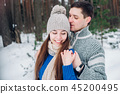 Young couple hugging and kissing in the forest in winter. 45200495