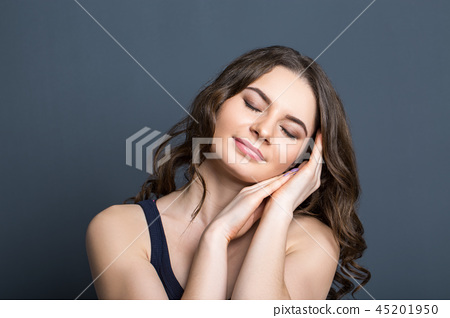 Beautiful young girl on a gray background smiling 45201950
