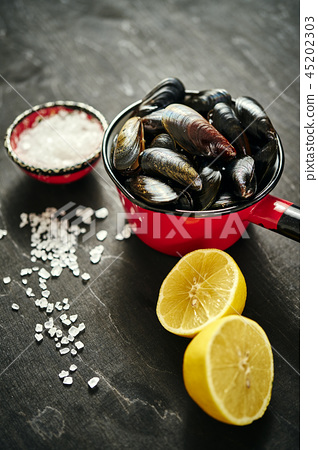 fresh, delicious raw mussels in a saucepan with salt and lemon 45202303