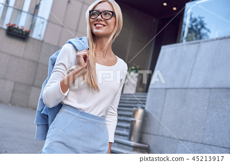 Young pretty spectacled businesswoman smiling and walking near business building 45213917