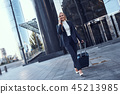 Full length portrait of a smiling successful businesswoman pulling suitcase 45213985