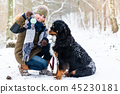 Woman walking Bernese mountain dog on a winter day 45230181