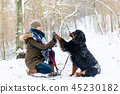 Woman and dog giving high-five in the snow 45230182