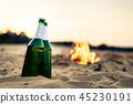 Two alcohol bottles on beach 45230191