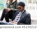 Young man sitting with his girlfriend using mobile 45230212