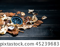 golden compass put on dried leaves on  wooden 45239683