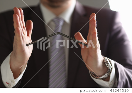 Man in suit and tie bend nail with arms closeup 45244510
