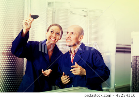 Coworkers looking at wine in glass 45254310