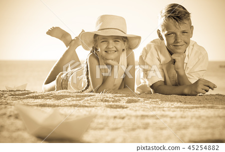 two kids lying beach 45254882