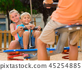 Children are teetering on the swing 45254885