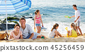 Couple relaxing on beach while their kids playing active games 45256459