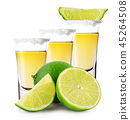 Three glasses of golden tequila with whole and sliced lime stand 45264508