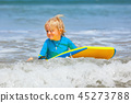 Little child swimming with bodyboard on sea wave 45273788