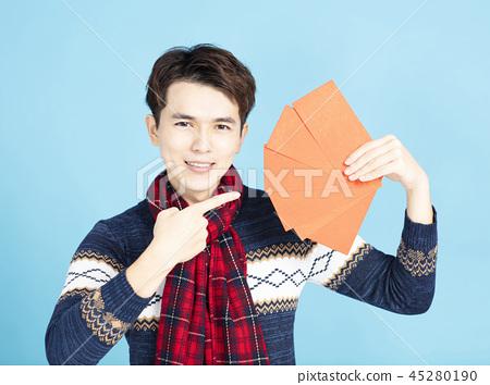 smiling asian man showing the red envelope 45280190