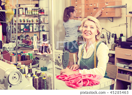 Two women sewing with professional equipment 45285463