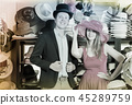 Glad woman and man trying on fashion hats 45289759