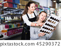 Young female hairdresser with woman client looking samples of hair dye in beauty salon 45290372