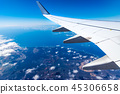 Wing of airplane above island with blue sky 45306658