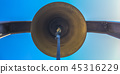 Bronze bell with blue rope beneath blue sky 45316229