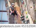 Man climber on artificial climbing wall 45332094