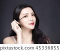 woman applying black eye mascara to her eyelashes 45336855