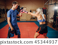 Female kickboxer on workout with personal trainer 45344937