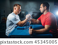 Arm wrestlers fighting, dust from talc in the air 45345005