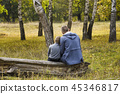 Father and son are sitting in the autumn forest 45346817