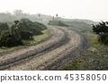 Misty winding gravel road 45358050