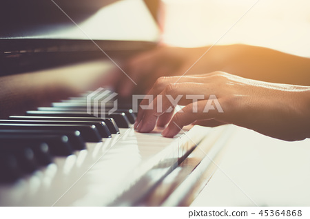 Close up of happy woman's hand playing the piano in the morning. 45364868