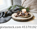Winter festive still life scene. Burning candle decorated by wooden stars, hazelnuts and pine cones 45370192