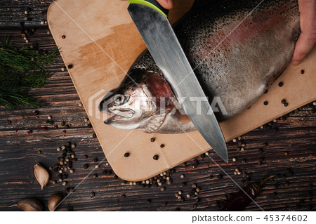 trout on the Board with a knife cutting it for cooking 45374602