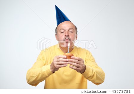 Mature man blowing candle on his cake 45375781