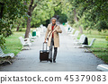 Mature businessman with suitcase walking in a park in a city, checking the time. 45379083