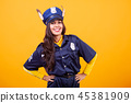 Beautiful young woman wearing Police costume over yellow background 45381909