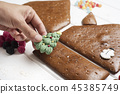 young man making a gingerbread house 45385749