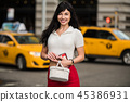 woman waiting for yellow taxi on city street  45386931