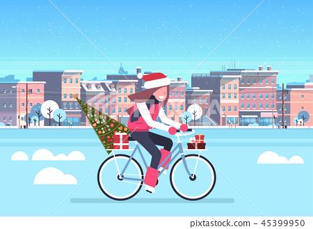 woman riding bike with fir tree gift box over city street buildings cityscape background merry 45399950