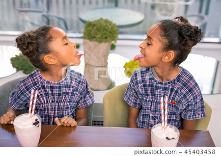 Two curly dark-haired siblings playing tricks spending time in kids cafe 45403458