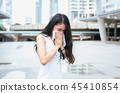 Woman sneeze on street because pollution outdoor 45410854