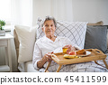A sick senior woman with food on a wooden tray lying in bed at home. 45411599