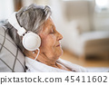 Sick senior woman with headphones lying in bed at home or in hospital. 45411602