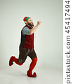friendly man dressed like a funny gnome posing on an isolated gray background 45417494