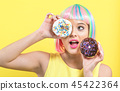 Beautiful woman in a colorful wig with donuts 45422364