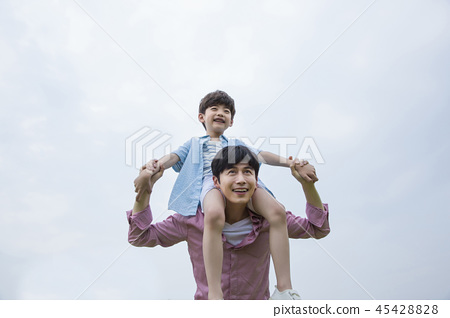 Family having picnic outdoors. Parents with two children relax in the park. Concept of happy family relations and carefree leisure time. 075 45428828