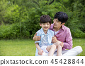 Family having picnic outdoors. Parents with two children relax in the park. Concept of happy family relations and carefree leisure time. 086 45428844