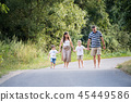 A family with two small sons walking barefoot on a road in park on a summer day. 45449586