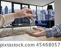 Realtor giving key to buyer in Modern living room 45468057